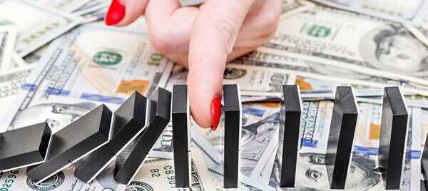 Female hand stopping domino effect on dollar backgrounds. Business concept.